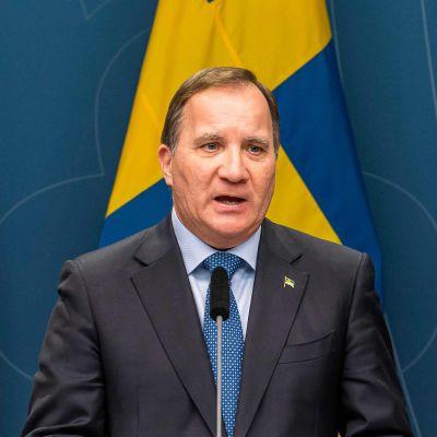 Sveriges statsminister Stefan Löfven talar i en mikrofon. Bakom honom syns Sveriges flagga.