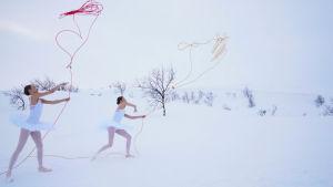 Kaksi ballerina-asuista tyttöä heittää köyttä lumisella tunturilla.