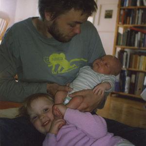 Nuori isä sylissään vauva ja vauvan jalkoihin nojaamassa pieni tyttö.