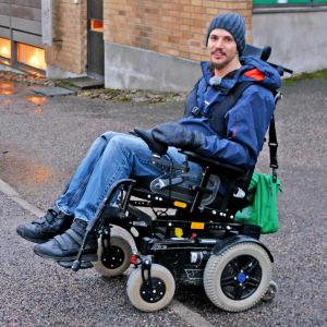 Jonas ute på gatan, försöker ta sig upp på en trottoarkant med rullstolen.