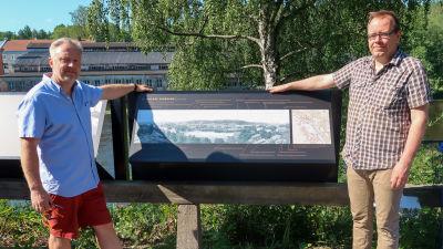 Porträtt av Kim Björklund och Aapo Roselius vid en skylt med ett gammalt fotografi av Billnäs.