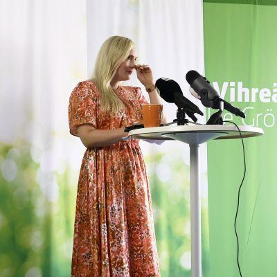 Maria Ohisalo torkar bort tårar medan hon håller presskonferens.