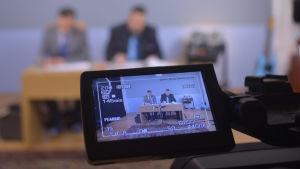 André Wickström och Stan Saanila syns i tv-kamerans skärm samt utan fokus själva i bakgrunden