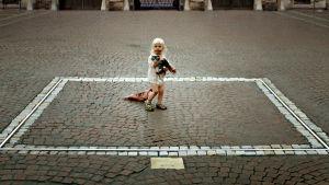 Pieni tyttö ja kissa taideneliössä. Kuva elokuvasta The Square.