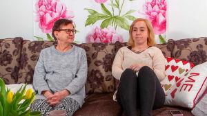 Marja ja Eija istuvat sohvalla.