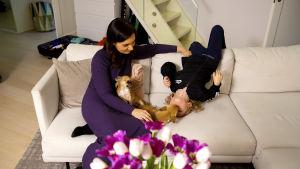 Johanna Pihlajamäki sohvalla pojan ja koiran kanssa