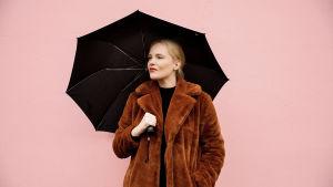 Artisti Titta Hakala seisoo mustan sateenvarjon alla vaaleanpunaisen seinän edessä. Hän katsoo vasemmalle.