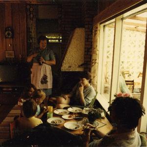 Kolme lasta ja kaksi aikuista istuvat ruokapöydän ääressä mökillä. Yksi aikuinen seisoo katselemassa ruokailijoita.
