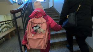 Lapsi ja äiti nousevat koulun rappusia.