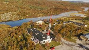 Valkoinen rakennus, jolla musta katto. Katolla useita metrejä korkea antenni. Rakennus sijaitsee joen varrella, pienen tunturin juurella.