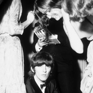 Gerorge Harrison i The Beatles skriver autografer i London 29.7.1965 på premiären av filmen Help!
