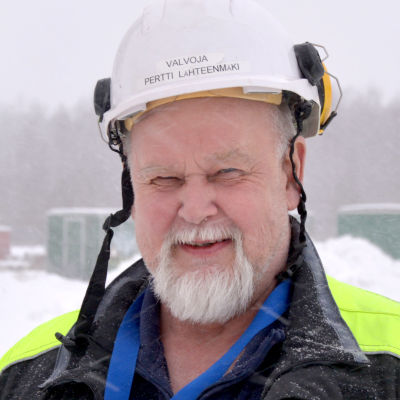 Skäggig man i gul reflexjacka och skyddshjälm står framför en snödriva
