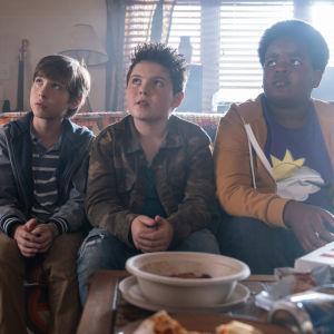 Trion i Good Boys sitter på en soffa och blickar uppåt.