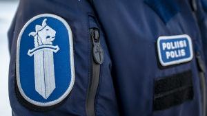 Närbild av polis i uniform. Texten poliisi polis syns på bröstet och på överarmen finns polisens emblem bestående av ett svärd och ett krönt  lejonhuvud.