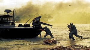 Män springer på stranden mot en armébåt samtidigt som det är rök i luften.