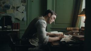 Tolkien (Nichols Hoult) sitter och skissar vid sitt skrivbord.