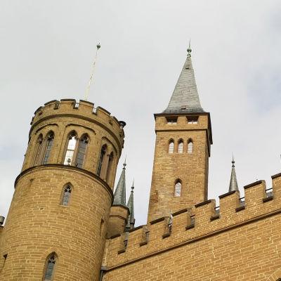 Familjens säte Burg Hohenzollern ligger uppe på ett berg och har många torn.