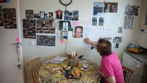 nainen katselee kotinsa seinää, jossa on paljon kuvia