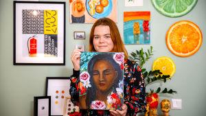 Emmi Kataja pitelee käsissään maalaamaansa taulua naisesta, jolla on silmät kiinni. Taustalla näkyy olohuoneen seinä, johon on ripustettu useita Emmin maalaamia tauluja.