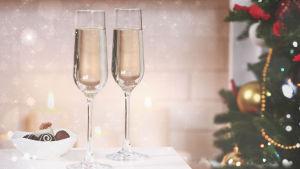 Pöydällä on kaksi kuohuviinilasia, valkoisessa kulhossa suklaakonvehteja, oikeassa värikäs joulukuusi. Pöydän taustalla valkoiset kynttilät.