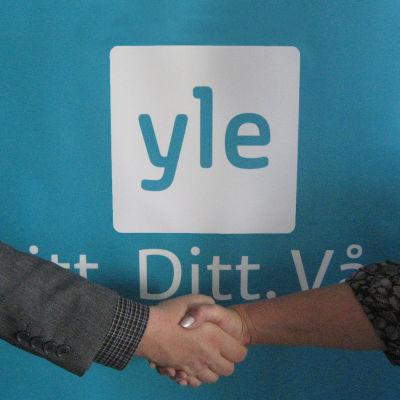 två händer som hälsar och en logo