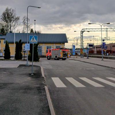 En brandbil står parkerad utanför en gul träbyggnad som är en järnvägsstation. Till höger löper järnvägsspåren.