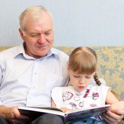 Äldre man och flicka läser en bok tillsammans i soffan.