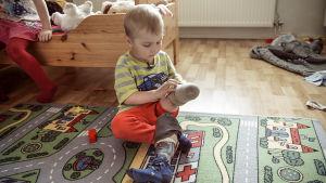 Luca-Emil Mykkänen istuu huoneensa lattialla ja asettelee sääriproteesia jalkaansa.