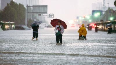 Ihmisiä kadulla tulvassa.