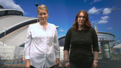 Två kvinnor står framför en bild av en byggnad
