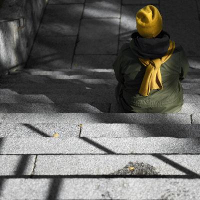 Nainen istuu yksin puiston portailla.