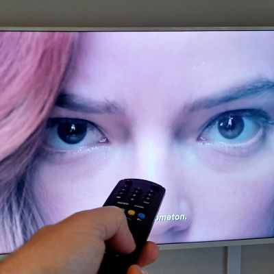 Musta kuningatar -televisiosarja televisiossa ja etualalla käsi, joka pitää kaukosäädintä.