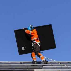 Aurinkopaneeleja kannetaan omakotitalon katolla.