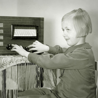 Pikkutyttö (Kirsti Nikulainen) kuuntelee radiota (1930-luku).