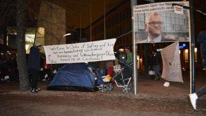 tältdemonstration utanför kiasma ,banderoll om att sipilä erbjöd flyktingar sitt hus