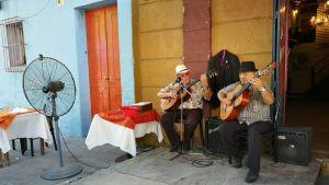 Två herrar spelar traditionell musik utanför en restaurang i Buenos Aires.