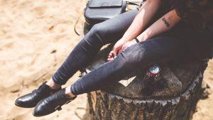Flicka sitter på stubbe