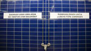 Bild från simhall med texten: Saunaan ilman uima-asua / Gå i bastun utan baddräkt och Suihkuun ennen uintia / Duscha före simningen.