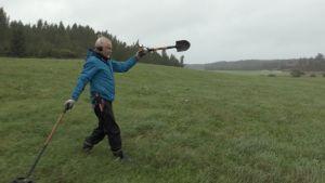 Reijo Hyvönen (Menneisyyden metsästäjät) niityllä lapion kanssa