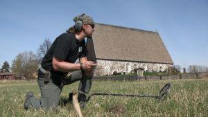 Mikko Mäkelä (Menneisyyden metsästäjät) kirkon edessä pellolla