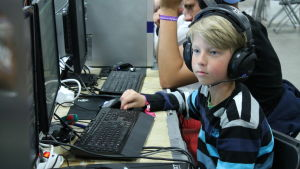 Ung pojke sitter vid en dator.