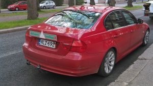 En röd bil med bilskolans vita triangel på bakluckan