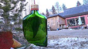 särkynyt pullo on ripustettu oksalta roikkumaan