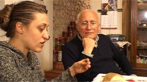 aikuinen tytär ja isä istuvat pöydän äärellä keskustelemassa