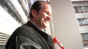 mies hymyilee kerrostalon sisäpihalla