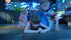Kolme lasta voimistelee. Tyttö ryömii pojan jalkojen alta.