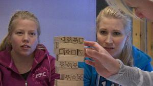 Maija Salmiovirta och Oona Kauste följer Sanna Puustinens drag i tornspelet.