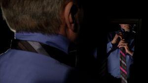 Anonyymi mies solmii solmiota peilin edessä dramaattisesti valaistuna.