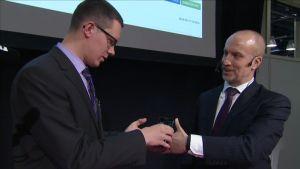 Henry Brade lataa Pekko Vehviläisen käden siruun 5 euron arvosta Bitcoineja (24.2. 2015 Messukeskus)