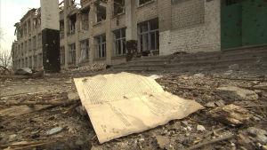 Tuhoutuneen koulun pihalla kirja
